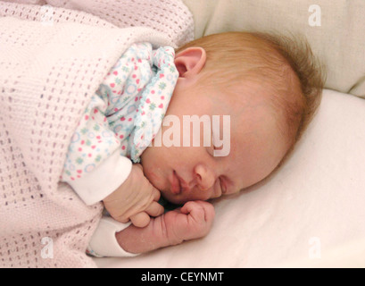 Female baby, weeks old, wearing a babygro, lying on her side, sleeping - Stock Photo