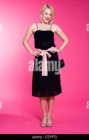Female bobbed blonde hair wearing knee length black dress pink ...