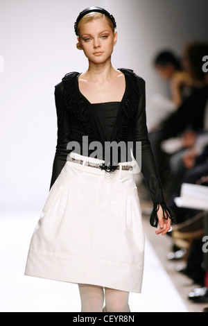 Anne Klein New York Ready to Wear Autumn Winter Model wearing white volume skirt, black long sleeve top fringed - Stock Photo
