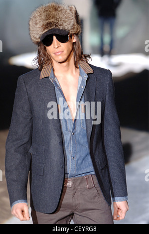 Iceberg Menswear Milan A W Brunette male long hair wearing a grey pin striped blazer over a denim brown trim button - Stock Photo