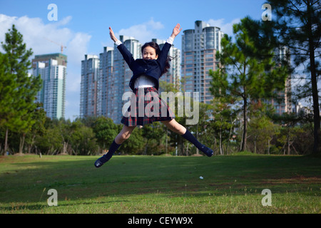 schoolgirl jumping in a park - Stock Photo