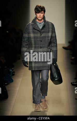 Bottega Veneta Milan Menswear Ready to Wear Autumn Winter Oversize checked coat, blue jeans, gloves, black leather - Stock Photo