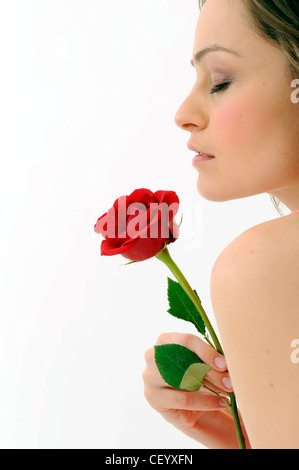 Female with brunette hair, holding a single red rose with one hand, unsmiling, breathing in the smell of rose - Stock Photo