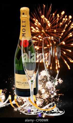 Two champagne glasses next to an unopened champagne bottle with gold streamers around them with fireworks in the - Stock Photo