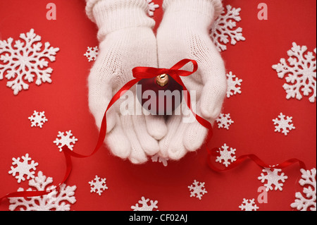 christmas ball in hands on red background with snowflakes - Stock Photo