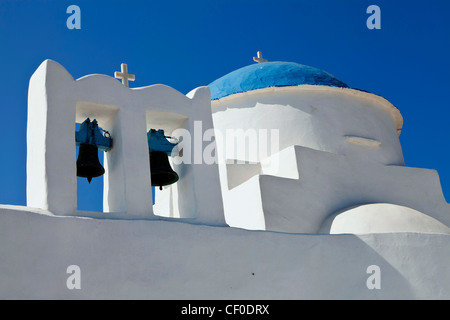traditional Sifnos island small white church with a blue dome, white crosses and old copper made bells shoot on - Stock Photo