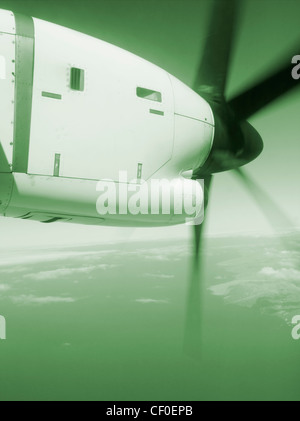 Airplane propeller from window seat of twin prop plane - Stock Photo