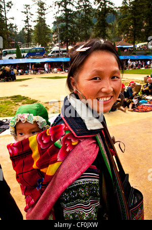 An Hmong hill tribe mother and baby in a tourist market Sapa, Vietnam - Stock Photo