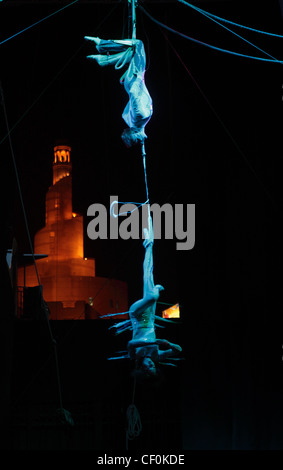 Trapeze artists  perform for the Doha Spring Festival at a stage in Souq Waqif, Doha, Qatar, in front of a spiral - Stock Photo