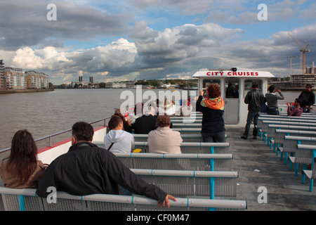 People sightseeing on a boat cruise on the River Thames, London, UK. Holiday tourism in Britain. - Stock Photo