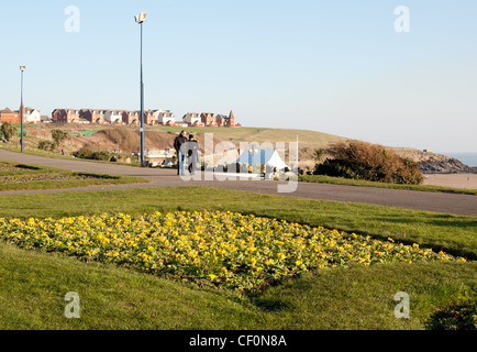 Couple walking along a beach front path at Barry Island South Wales, UK, location of filming Gavin & Stacey tv series - Stock Photo