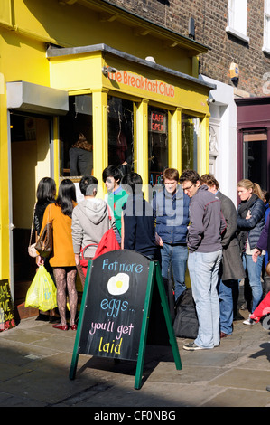 Queue of people outside The Breakfast Club Camden Passage, Islington London England UK - Stock Photo