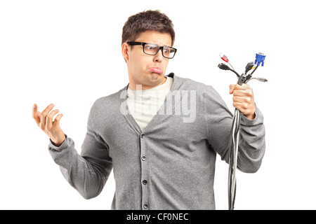 Confused young man holding a bunch of cables, isolated on white - Stock Photo