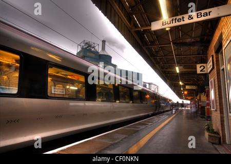 A Virgin train arriving at Bank Quay west coast mainline Railway Station, Warrington, Cheshire, UK at dusk - Stock Photo