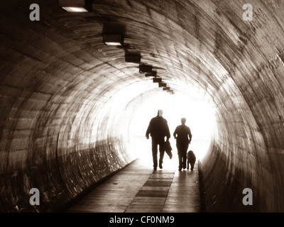 Two people and a dog walking through a tunnel at  Latchford (off Kingsway), Warrington , Cheshire , England, UK - Stock Photo