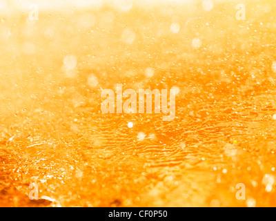Orange splashing liquid closeup abstract background texture - Stock Photo