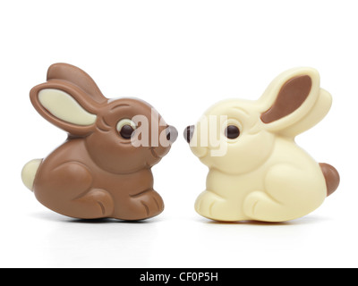 Two cute milk and white chocolate bunnies sitting nose to nose isolated on white background - Stock Photo