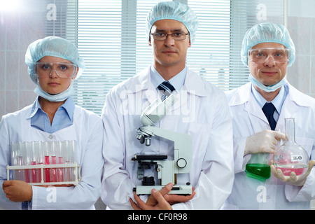 Three serious scientists holding lab equipment and looking at camera - Stock Photo