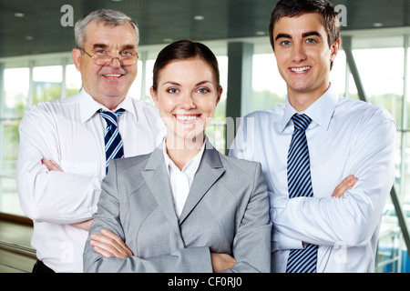 Three smiling business people looking confidently at camera - Stock Photo