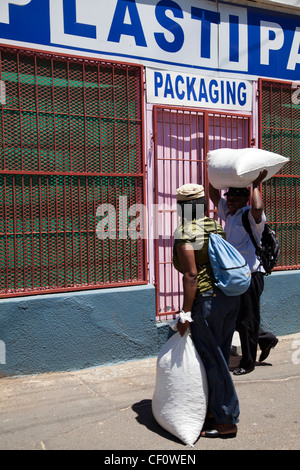 Two locals carry bags on head in Woodstock - Cape Town - Stock Photo