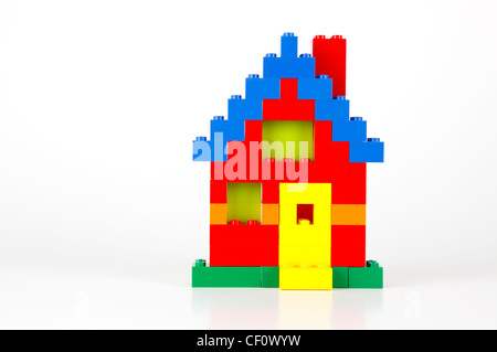 A house built of red, blue, yellow, and green traditional LEGO bricks on a white background with slight reflections - Stock Photo