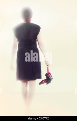 Woman in a black dress goes with red shoes in hand into the light - Stock Photo
