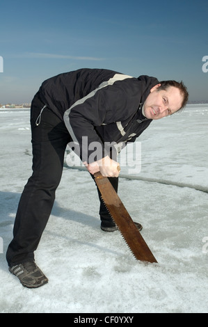Man sawing with a hand saw a diving hole. Preparations for subglacial diving, ice diving in the frozen Black Sea - Stock Photo