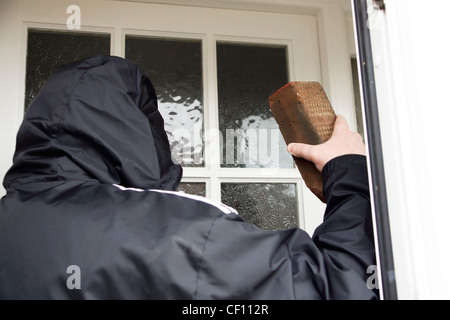 Undesirable character rogue hoodie smashing a brick through a glass window pane MODEL RELEASED - Stock Photo