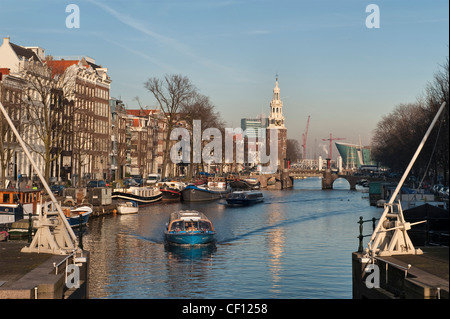 Amsterdam. A tourist boat on the Oude Schans canal, with the 16c Montelbaans Tower (Montelbaanstoren) in the background - Stock Photo