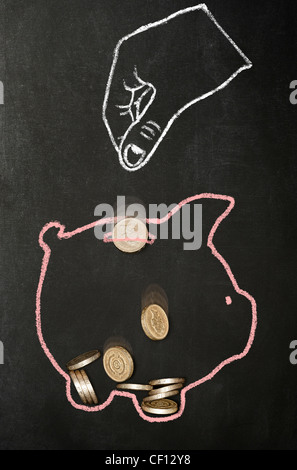 Chalk drawn hand dropping real pound coins into a chalk drawn piggy bank - Stock Photo