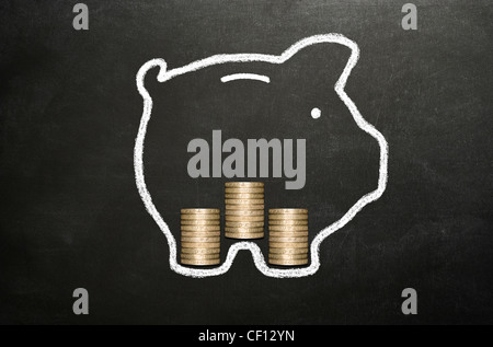 Piggy Bank drawn in chalk on a blackboard with three stacks of real pound coins inside it. - Stock Photo