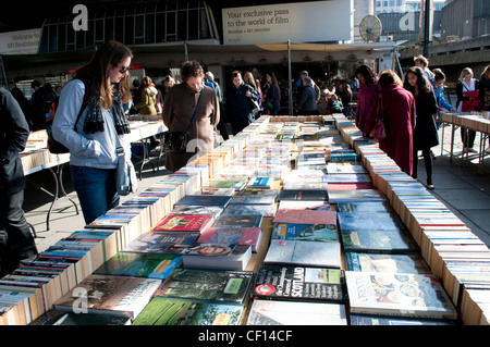 People browsing books at second-hand bookstalls under the Waterloo Bridge, , South Bank, London, UK - Stock Photo