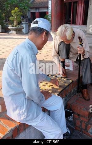 Two men playing Xiangqi Chinese chess game, Jade mountain temple, Hanoi, Vietnam - Stock Photo
