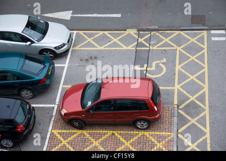Cars parked in disabled parking spaces in a car park - Stock Photo