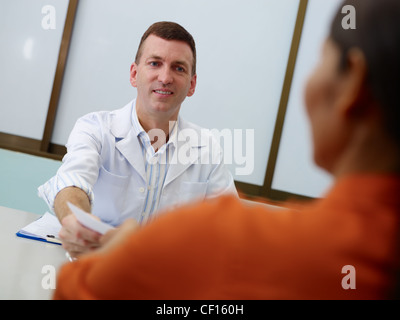Friendly doctor working and giving assistance to female mature patient in hospital office, writing prescription - Stock Photo