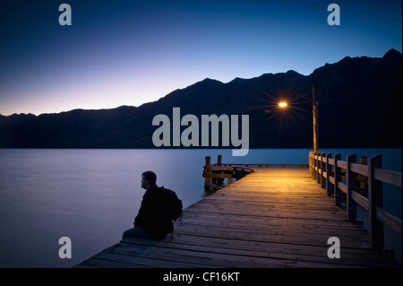 A Man Wearing A Backpack Sits On The Edge Of A Wooden Dock Illuminated With A Light At Dusk; Glenorchy South Island - Stock Photo