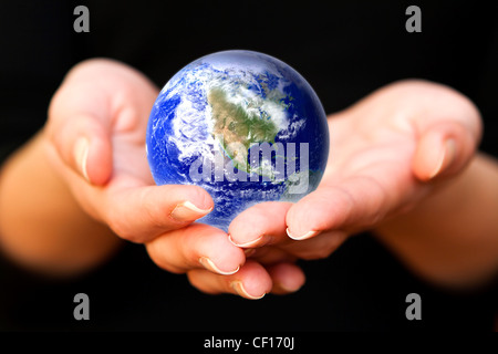 human hands carefully holding Earth planet. Glass World - Stock Photo