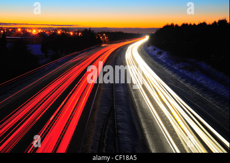 Traffic light trails on the M8 motorway in Scotland between Glasgow and Edinburgh. Taken at night in the winter with snow on the ground