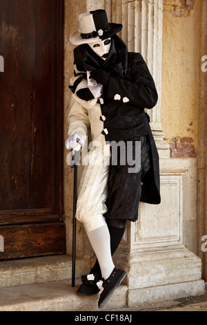 A man with a walking stick dressed up for Venice Carnival, Italy - Stock Photo