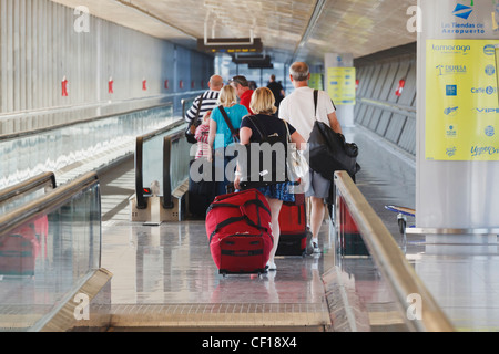 Tourists With Luggage Heading For The Departure Lounge At Malaga Airport; Malaga Province Costa Del Sol Spain - Stock Photo