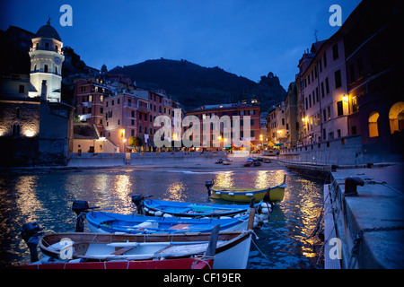 Boats Moored By Buildings Along The Waterfront At Night; Vernazza Liguria Italy - Stock Photo