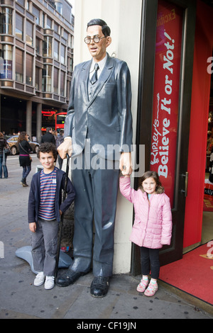 Model of Robert Wadlow (tallest man) with two small children outside Ripley's 'Believe it or Not' museum, Piccadilly, - Stock Photo