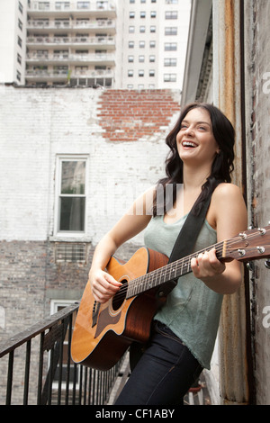 Woman playing guitar on fire escape - Stock Photo