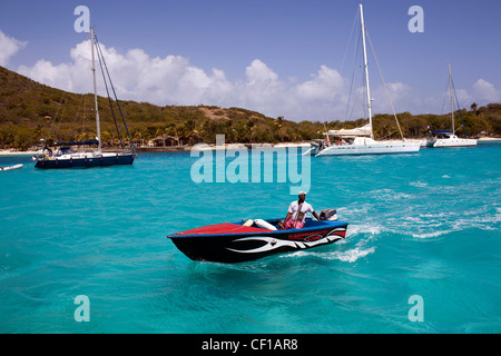 A local motorboat cruises through sailboats moored off the private island of Petit St. Vincent, or PSV. - Stock Photo