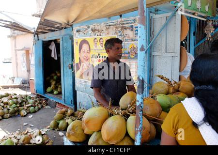 a street vendor selling tender coconuts at kanyakumari, india. In the backdrop is a political graffiti. - Stock Photo