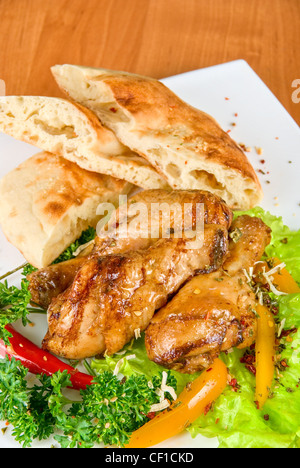 roasted chicken drumstick garnished with fresh green salad, pepper and greens - Stock Photo