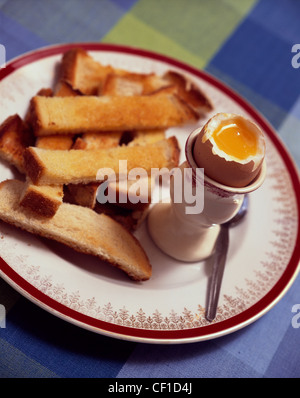 A soft boiled egg in and egg cup with white buttered toast cut into soldiers - Stock Photo