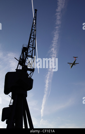 A plane flying over the silhouette of a derelict crane at Royal Victoria Dock in the redeveloped Docklands area - Stock Photo