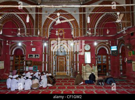 Men praying inside the Jamaat Khana Masjid  close to the tomb of the Sufi saint Nizamuddin  (Nizamuddin Dargah), - Stock Photo