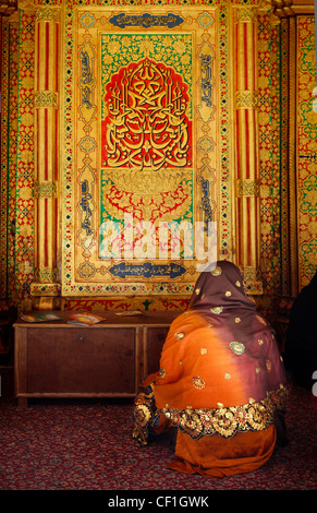 A  muslim woman praying in front of  the Mausoleum of the Sufi saint Nizamuddin Auliya (Nizamuddin Dargah), Delhi, - Stock Photo
